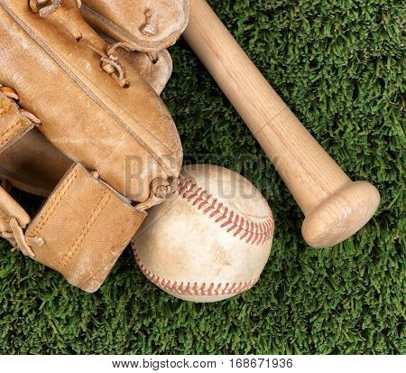 Flat view of old baseball mitt ball and bat on grass