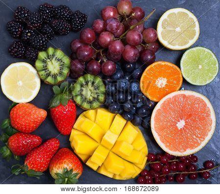 Raw fruit and berries platter mango kiwis strawberries blueberries blackberries red currants grapes top view