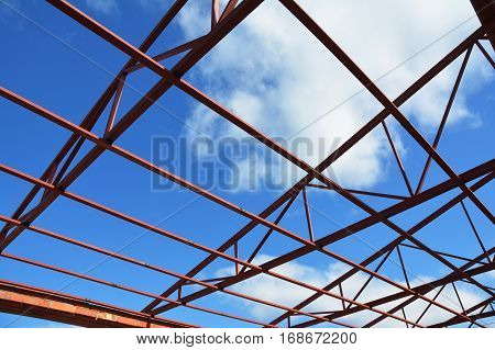 Steel roof trusses details with clouds sky background. Steel roof trusses sitting on concrete pole view from inside home factory with copy space.