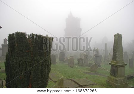 Spooky Grave yard with Yew Shrub in foreground and church outline in mist.