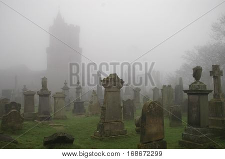Spooky Grave yard with church outline in mist.