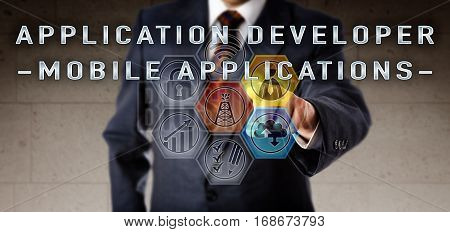 Recruitment manager in blue business suit touching APPLICATION DEVELOPER - MOBILE APPLICATIONS on an interactive virtual remote control screen. Software development job concept for oil and gas.