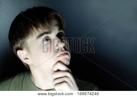 Thoughtful Young Man Portrait In Dark Background