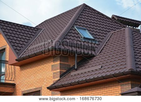 New roofing construction with attic skylights rain gutter system roof windows and roof protection from snow board snow guard exterior. Modern House Construction. Hip and Valley roofing types.