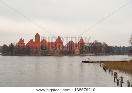 The view to lake and Trakai Peninsula Castle Museum on the island. Girl standing on the pier and taking photos on her phone. Village of Karaites, Lithuania, Europe. Lithuanian landmark in late autumn