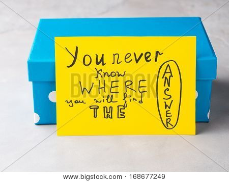 Yellow card spelling hand written words You never know where you will find the Answer on blue gift box.