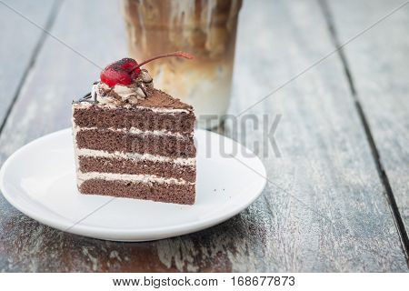 chocolate cake with cherry topping and ice coffee mocha in outdoor cafe