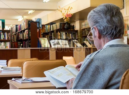 Sosnovy Bor, Russia - March 22 2016: Elderly man reading a magazine in the reading room of the library