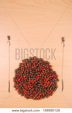 Fishing bait with hook and brown with red pre-drilled halibut pellets for carp fishing isolated on wood background with soft shadow