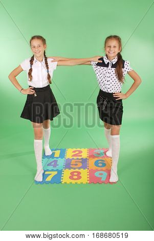Two girls on rug with numbers one two three four five six seven eight nine on green background