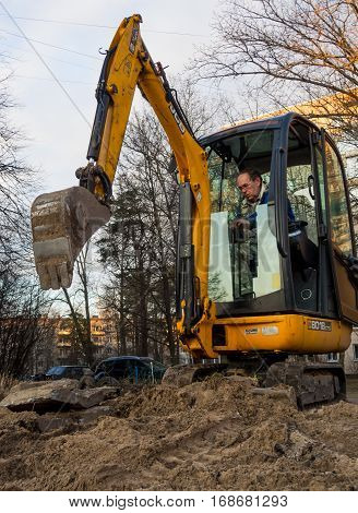 Sosnovy Bor, Russia - April 7 2016: Mini excavator digging a trench under the city communications