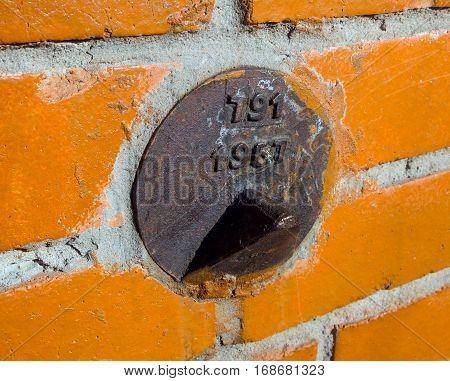 Geodetic mark (sign) on the brick wall of the house