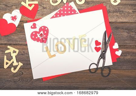 Vintage Valentine and loved themed scrapbooking background, with cutout hearts, wooden letters spelling LOVE, scissors and craft paper. Filtered to look like an old photo, nostalgic style.