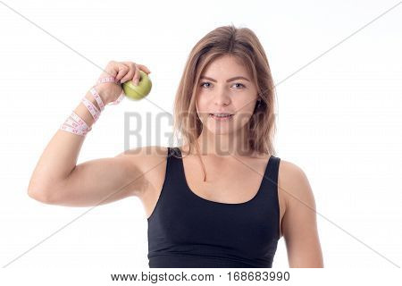 Beautiful athletic girl shows muscles clenching an apple in his hand and erase directly