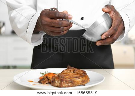 African American chef cooking tasty meat in kitchen, closeup