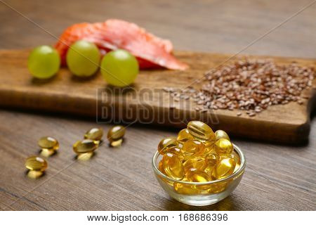 Fish oil pills, flax grain, grape and fish fillet on wooden background