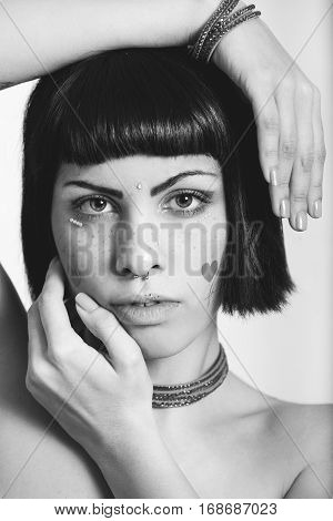 Portrait of young woman with freckles and heart-shaped stickers. Hands geometric position. Black and white