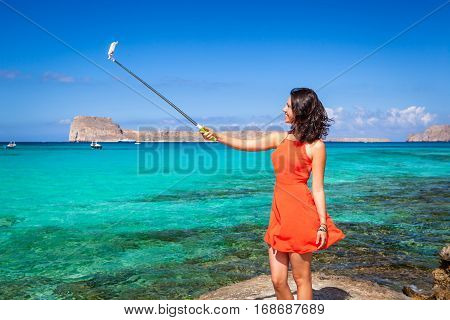 Pretty young model dressed in a coral clothes having fun making selfie with a selfiestick on the background of the clear blue sea