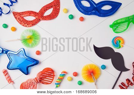 Carnival party concept with costume mask and glasses on white background. Top view from above