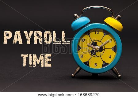 Concept,alarm Clock With Payroll Time Phrase Written On Black Background