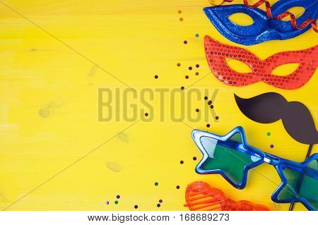Carnival party concept with costume mask and glasses on yellow background. Top view from above