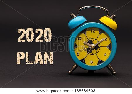 2020 Plan Written With Alarm Clock On Black Paper Background