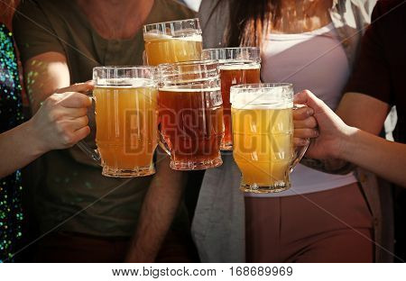 People clinking mugs with beer in pub, closeup