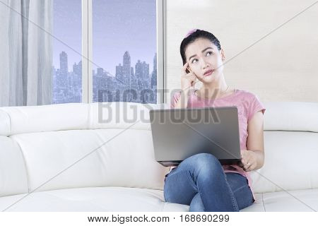 Beautiful female model sitting on the cozy sofa while daydreaming and using a laptop shot in the living room
