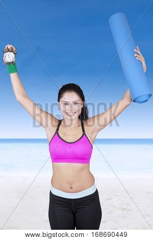 Portrait of beautiful woman holding a watch and mattress while standing in the beach