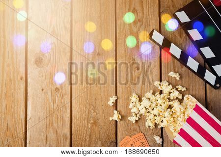 Movie clapper board and popcorn on wooden background. Cinema concept. Top view from above