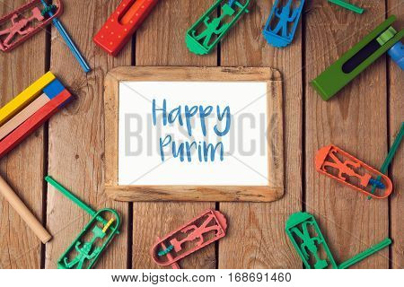Purim holiday concept with blank photo frame and noisemakers on wooden background. Top view from above