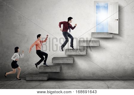 Three young businesspeople running on the stairs and compete to reach an opportunity door to success