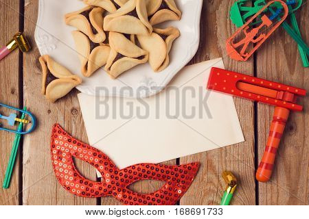 Purim holiday concept with greeting card and hamantaschen cookies on wooden background. Top view from above