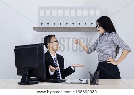 Portrait of young businesswoman shouting to her subordinate while standing in the office