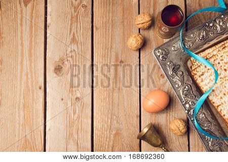 Jewish holiday Passover concept with matzah seder plate and wine on wooden background. View from above
