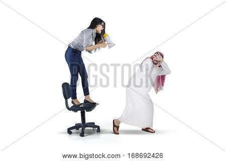 Picture of businesswoman yelling to her arabian subordinate with megaphone while standing on the chair isolated on white background