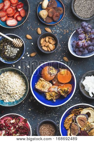 Ingredients in bowls for healthy breakfast over dark blue background, top view. Fresh and dried fruit, chia seeds, oatmeal, nuts, honey. Clean eating, vegan, vegetarian, detox and dieting concept