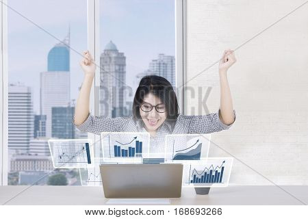 Picture of cheerful female worker expressing her success in the office while looking at profit graph on the laptop