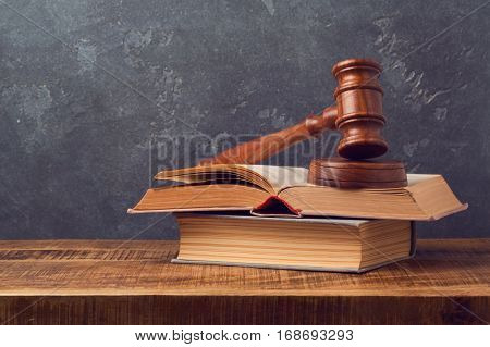 Open law book with judges gavel on wooden table. Courtroom or law enforcement office concept