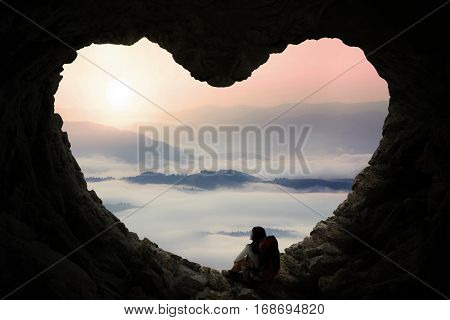 Silhouette of female backpacker enjoy mountain view while sitting inside cave shaped heart symbol