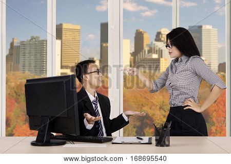 Portrait of female entrepreneur pointing to her subordinate as angry expression with autumn background on the window