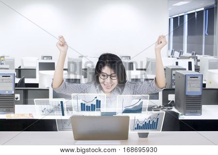 Photo of happy female entrepreneur looking at virtual profit statistics on the laptop in the office