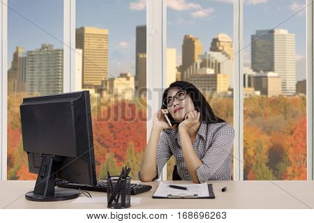 Female worker daydreaming while listening on her cellphone with autumn background on the window