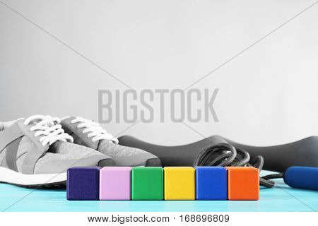 Multicoloured cubes with space for text, jogging shoes and dumb-bells on grey background