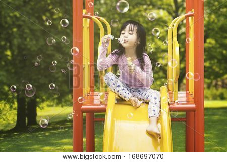 Cute little girl sitting on the slide while blowing soap bubbles shot at the playground