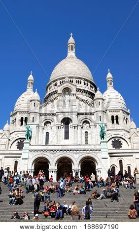 PARIS, FRANCE - APRIL 27, 2006: Tourists stroll in Montmartre near Basilica Sacre Coeur (designed by Paul Abadie 1914) - Roman Catholic Church and minor basilica dedicated to Sacred Heart of Jesus.