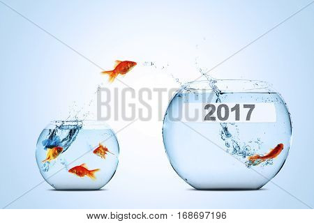 Golden fish leaping to larger fishbowl with number 2017 isolated on white background