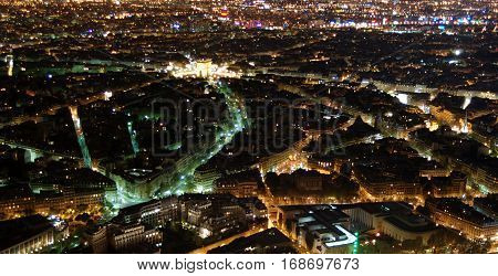 Night Paris seen from 300 m above ground from the top of the Aiffel Tower with the Arc de Triumph glowing at the back