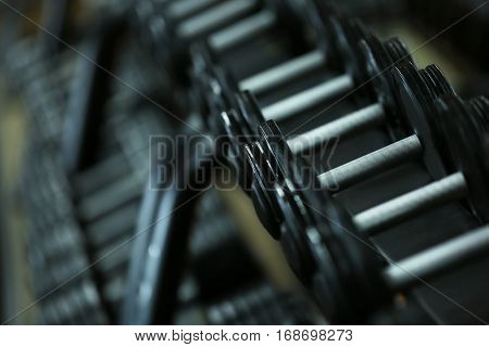 Rack with dumbbells in gym, close up view