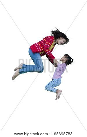 Young mother and child leaping together in the studio isolated on white background